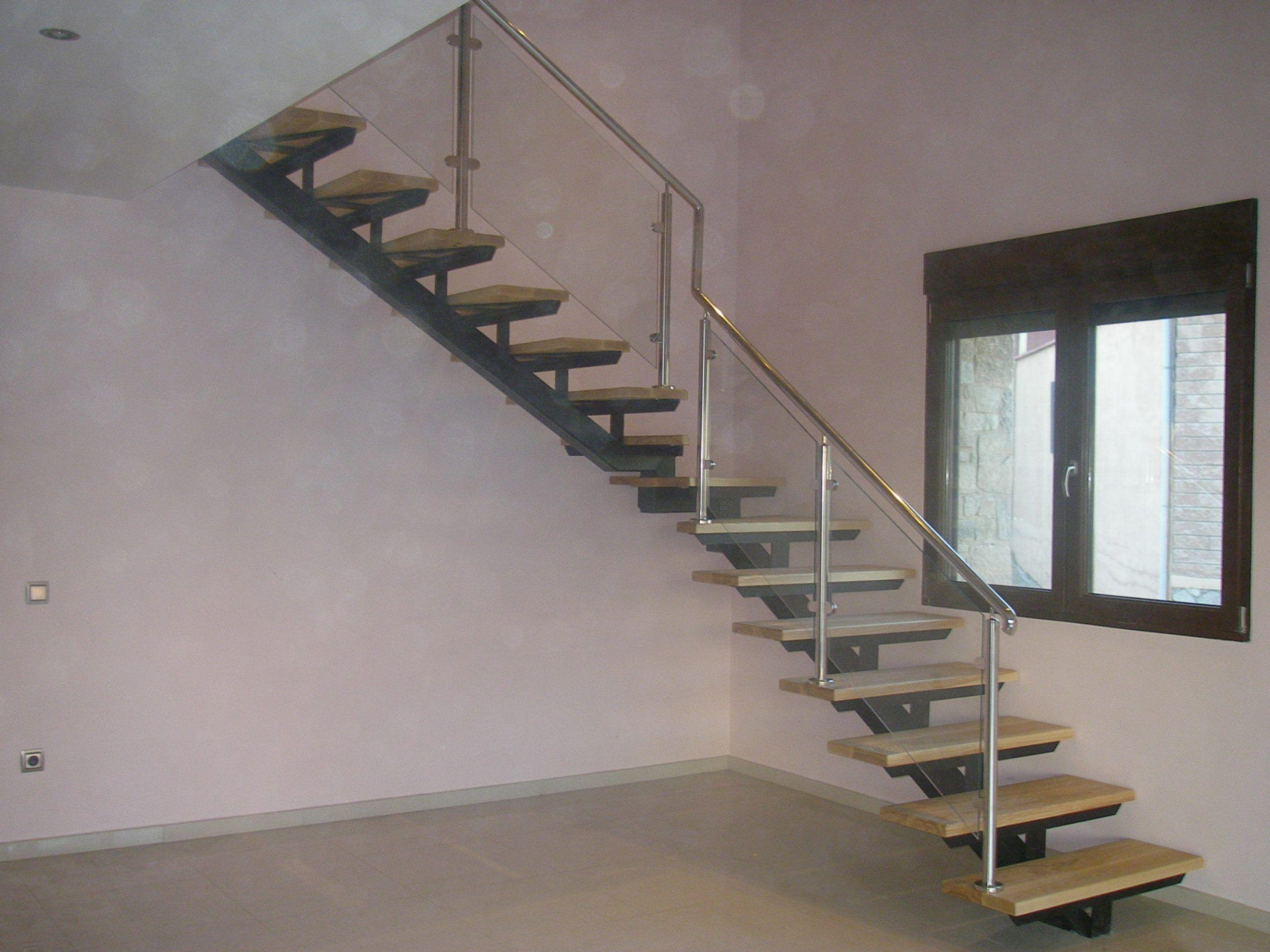 Escalera con pasos de madera y pasamanos en acero inxodable y cristal